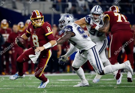 Kirk Cousins, DeMarcus Lawrence. Washington Redskins quarterback Kirk Cousins (8) scrambles out of the pocket escaping pressure from Dallas Cowboys defensive end DeMarcus Lawrence in the first half of an NFL football game, in Arlington, Texas