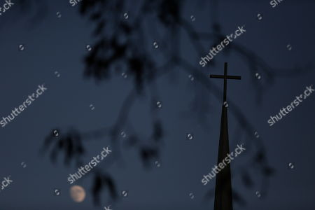 Stock Photo of The moon and a cross are seen at Bryan Baptist church, in Dora, Ala