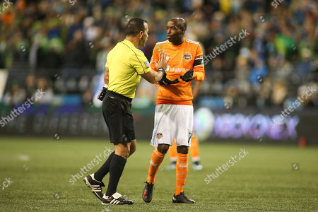 Stock Image of Houston Dynamo defender DaMarcus Beasley (7) argues a red card on Toms Martnez with referee Hilario Grajeda during the second leg of the MLS Western Conference finals match between the Houston Dynamo and Seattle Sounders at CenturyLink Field in Seattle, WA. The Seattle Sounders defeated the Houston Dynamo 3-0