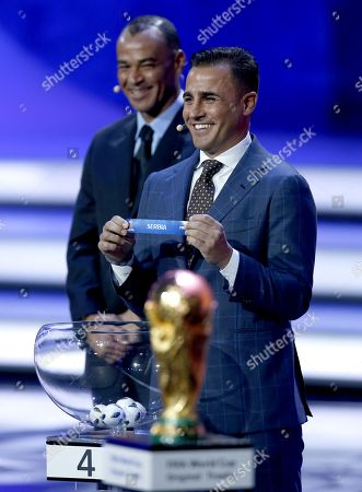 Former Italian international Fabio Cannavaro (R) shows the ticket of Serbia during the Final Draw of the FIFA World Cup 2018 at the State Kremlin Palace in Moscow, Russia, 01 December 2017. The FIFA World Cup 2018 will take place from 14 June until 15 July 2018 in Russia.