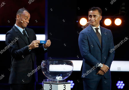 Former Brazilian soccer international Cafu holds up the team name of Sweden as former Italian soccer international Fabio Cannavaro looks on during the 2018 soccer World Cup draw in the Kremlin in Moscow