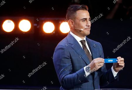 Former Italian soccer international Fabio Cannavaro holds up the team name of Japan during the 2018 soccer World Cup draw in the Kremlin in Moscow