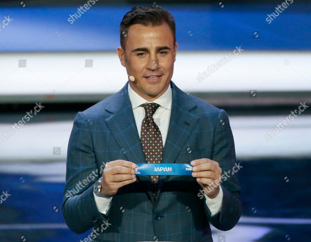 Former Italian soccer international Fabio Cannavaro holds up the team name of Japan at the 2018 soccer World Cup draw in the Kremlin in Moscow