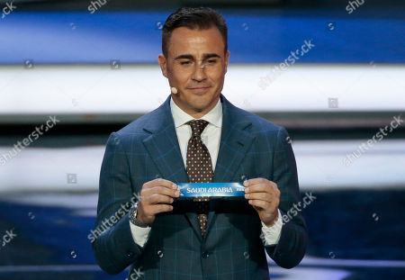 Former Italian soccer international Fabio Cannavaro holds up the team name of Saudi Arabia at the 2018 soccer World Cup draw in the Kremlin in Moscow