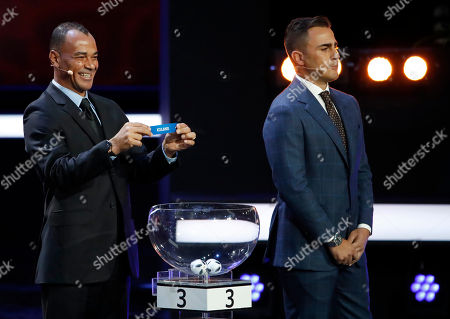 Former Brazilian soccer international Cafu smiles holding up the team name of Iceland as Former Italian soccer international Fabio Cannavaro looks on during the 2018 soccer World Cup draw in the Kremlin in Moscow