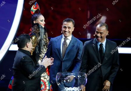Argentine soccer legend Diego Maradona, former Italian soccer international Fabio Cannavaro and former Brazilian soccer international Cafu, from left, joke on stage during the 2018 soccer World Cup draw in the Kremlin in Moscow