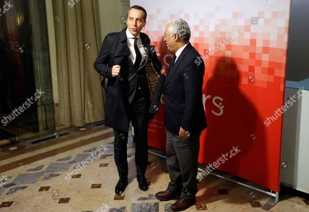 Austria Chancellor Christian Kern takes off his coat to pose for photos with Portuguese Prime Minister Antonio Costa before a dinner at the Portuguese Socialist Party headquarters in Lisbon, . European Socialist leaders are in Lisbon to attend the Party of European Socialists Council Friday and Saturday