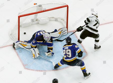 Los Angeles Kings' Tyler Toffoli scores past St. Louis Blues goalie Carter Hutton and Vince Dunn (29) during the first period of an NHL hockey game, in St. Louis