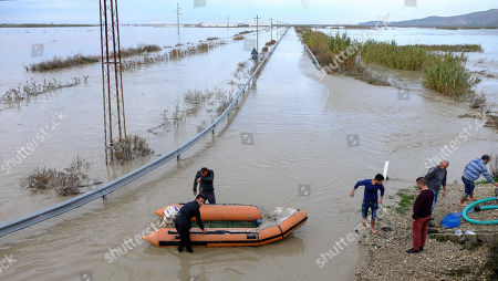 Albanian emergency responders help to evacuate people at Ferras village near Ura e Mifolit (Mifoli Bridge), Vlora district, 120 kilometers (75 miles) southwest of the capital Tirana, after non-stop rain caused Vjosa riverbanks to burst in the south of the country, . At least one person has died in the last three days of heavy rainfall that has flooded many parts of Albania, temporarily paralyzing its ports and suspending flights from its only international airport