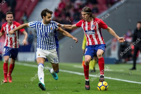 Stock Photo of Atletico Madrid's Brazilian defender Filipe Luis (R) duels for the ball with Real Sociedad's midfielder Xabi Prieto (C) during the Spanish Liga Primera Division soccer match played at Wanda Metropolitano stadium, in Madrid, Spain, 02 December 2017.