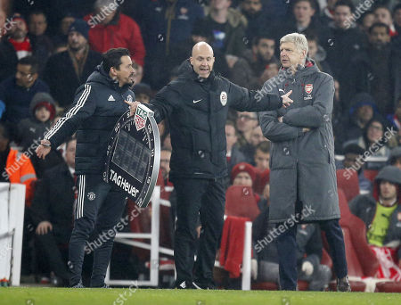 4th Official Andre Marriner steps in to seperate Rui Faria (left) the Manchester United assistant manager and Arsene Wenger the Arsenal manager