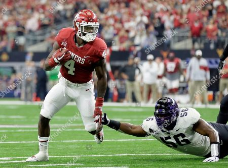 Stock Picture of Trey Sermon, Chris Bradley. Oklahoma running back Trey Sermon (4) escapes a tackle attempt by TCU defensive tackle Chris Bradley (56) in the first half of the Big 12 Conference championship NCAA college football game, in Arlington, Texas