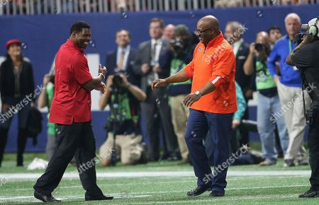 Former Auburn tailback Bo Jackson, right, and ex-Georgia star Herschel Walker speak during the first half of the Southeastern Conference championship NCAA college football game between Auburn and Georgia, in Atlanta. They were recognized on the field during a second-quarter time out. Jackson won the Heisman Trophy in 1985 and Walker captured it three years earlier