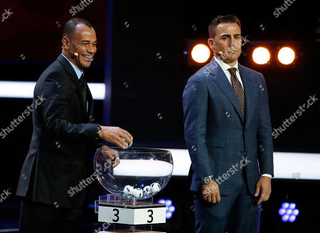 Former Brazilian soccer international Cafu, left, and former Italian soccer international Fabio Cannavaro assist during the 2018 soccer World Cup draw in the Kremlin in Moscow