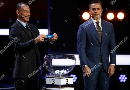 Former Brazilian soccer international Cafu holds up the team name of Iran as former Former Italian soccer international Fabio Cannavaro looks on during the 2018 soccer World Cup draw in the Kremlin in Moscow