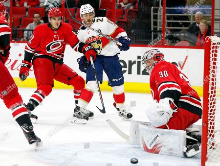 Stock Image of Trevor van Riemsdyk, Vincent Trocheck, Cam Ward. Florida Panthers' Vincent Trocheck (21) has his shot bounce off Carolina Hurricanes goalie Cam Ward (30) after beating Hurricanes' Trevor van Riemsdyk (57) during the first period of an NHL hockey game, in Raleigh, N.C