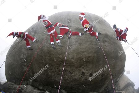 (L-R) South Korean rock climbers Choi Young-Sook, Lee Jae-Nam, Shim Kwon-Sik, Lee Se-Jung and Cha Ho-Eun, wearing Santa Claus costumes while rock- climbing during an event in the Christmas holiday season on the Bulam mountain in Seoul, South Korea, 03 December 2017.