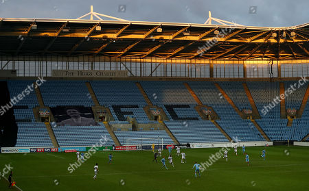 A general view of the action infront an empty stand with an image of the late Jimmy Hill