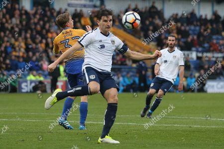 Stock Image of Ashley Palmer of Guiseley AFC (5) clears the ball during the The FA Cup match between Mansfield Town and Guiseley  at the One Call Stadium, Mansfield