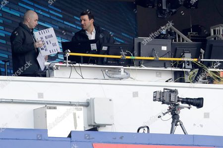 Former Dallas Cowboys quarterback Tony Romo, right, talks to a person inside the broadcast booth prior to an NFL football game between the Buffalo Bills and the New England Patriots, in Orchard Park, N.Y