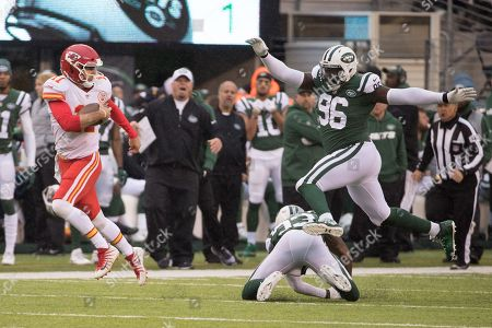 , 2017, Kansas City Chiefs quarterback Alex Smith (11) scrambles with the ball as he slips past New York Jets safety Jamal Adams (33) with defensive end Muhammad Wilkerson (96) leaping over him during the NFL game between the Kansas City Chiefs and the New York Jets at MetLife Stadium in East Rutherford, New Jersey. The New York Jets won 38-31