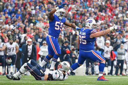 New England Patriots quarterback Tom Brady, bottom, lies on the ground after being sacked by Buffalo Bills defensive tackle Kyle Williams (95) during the first half of an NFL football game, in Orchard Park, N.Y. Bills' Jerry Hughes (55) reacts after the play