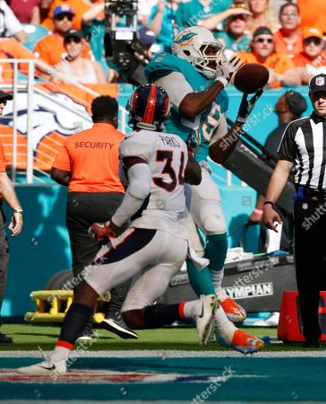 Julius Thomas, Will Parks. Miami Dolphins tight end Julius Thomas (89) grabs a touchdown pass as Denver Broncos defensive back Will Parks (34) defends, during the first half of an NFL football game, in Miami Gardens, Fla