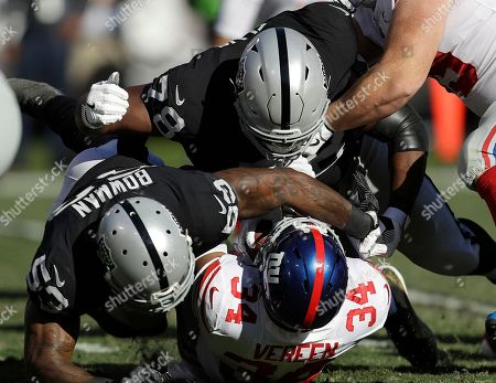 NaVorro Bowman, Justin Ellis, Shane Vereen. New York Giants running back Shane Vereen (34) is tackled by Oakland Raiders defensive tackle Justin Ellis (78) and linebacker NaVorro Bowman (53) during the first half of an NFL football game in Oakland, Calif