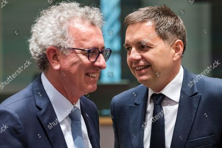 Luxembourg's Finance Minister Pierre Gramegna, left, talks with Slovakia's Finance Minister Peter Kazimir as they arrive for a meeting of eurozone finance ministers at the Europa building in Brussels on . Eurozone finance ministers meet Monday to elect a new president for the club of 19 nations that share the euro currency