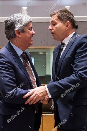 Slovakia's Finance Minister Peter Kazimir, right, greets Portugal's Finance Minister Mario Centeno as they arrive for a meeting of eurozone finance ministers at the Europa building in Brussels on . Eurozone finance ministers meet Monday to elect a new president for the club of 19 nations that share the euro currency