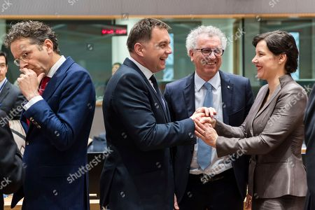 Latvia's Finance Minister Dana Reizniece-Ozola, right, talks with Slovakia's Finance Minister Peter Kazimir, 2nd left, and Luxembourg's Finance Minister Pierre Gramegna, 2nd right, as the Chair of the Eurogroup Jeroen Dijsselbloem walks by during a meeting of eurozone finance ministers at the Europa building in Brussels on . Eurozone finance ministers meet Monday to elect a new president for the club of 19 nations that share the euro currency