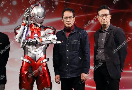 Japanese animation directors Kenji Kamiyama (C) and Aramaki Shinji (R) pose with the new Ultraman at the Tokyo Comic Con 2017 in Chiba