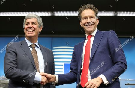 Portugal's Finance Minister Mario Centeno, left, shakes hands with president of the eurogroup Jeroen Dijsselbloem during a media conference after a meeting of eurozone finance ministers at the Europa building in Brussels on . The Eurogroup on Monday elected Portugal's Finance Minister Mario Centeno as the new president of the Eurogroup