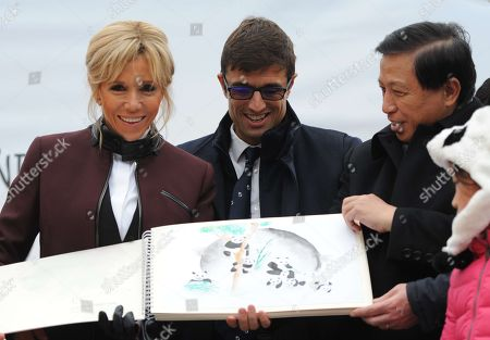 French President wife's Brigitte Trogneux and China's Vice Foreign Minister Zhang Yesui receive drawing of children during the panda cub's name ceremony.