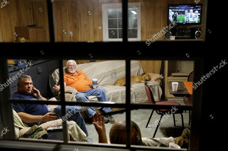 "Ricky Phillips, Buddy Jones, Cary Lewis. Cary Lewis, bottom right, and Ricky Phillips, left, watch an NFL football game at the home of Buddy Jones, during their weekly dinner gathering in Lumberton, N.C., . ""Every time I see one of his rallies on TV, he's doing a great job and bring people together,"" said Lewis, of Donald Trump whom he voted for after being a lifelong Democrat. ""And you got people who just like to keep things stirred up, and they don't want this country to have a good race relations"