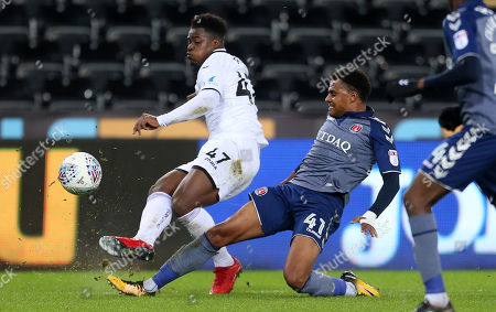 Tyler Reid of Swansea City is challenged by Jamie Mascoll of Charlton Athletic.