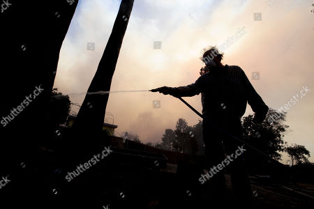 Homeowner Alan Barnard battles a hot spot from a wildfire in the Lake View Terrace area of Los Angeles on