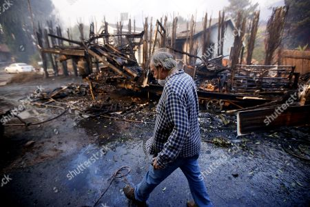Homeowner Alan Barnard walks past the remains of his RV from a wildfire in the Lake View Terrace area of Los Angeles on