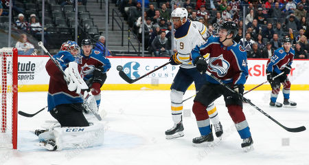 Buffalo Sabres left wing Evander Kane, center, swings at the puck as Colorado Avalanche goalie Semyon Varlamov, left, of Russia, tries to block the shot while defenseman Samuel Girard covers in the second period of an NHL hockey game, in Denver