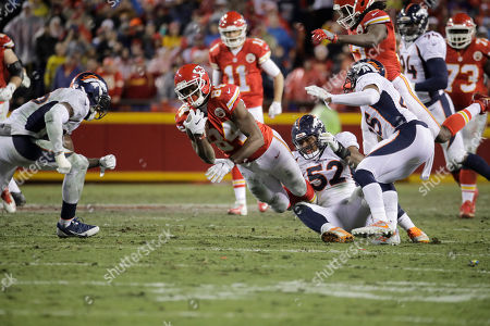 Kansas City Chiefs tight end Demetrius Harris (84) is tripped by Denver Broncos linebacker Corey Nelson (52) and cornerback Chris Harris Jr., right, during the first half of an NFL football game in Kansas City, Mo