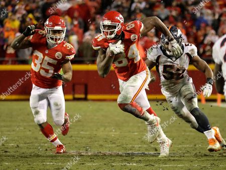 Kansas City Chiefs tight end Demetrius Harris (84) runs alongside running back Charcandrick West (35) away from Denver Broncos linebacker Corey Nelson (52) during the second half of an NFL football game in Kansas City, Mo