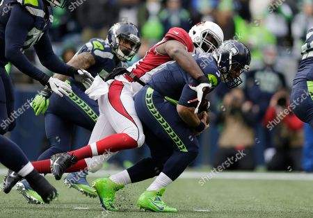 Seattle Seahawks quarterback Russell Wilson, right, is sacked by Arizona Cardinals' Chandler Jones in the first half of an NFL football game, in Seattle