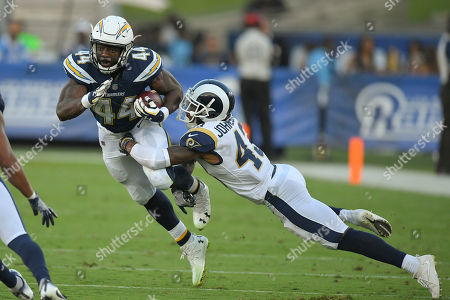 Los Angeles Chargers running back Andre Williams is brought down by Los Angeles Rams defensive back John Johnson during the second half of a preseason NFL football game, in Los Angeles