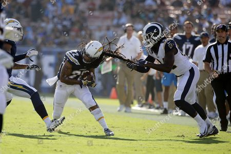 Los Angeles Chargers cornerback Jason Verrett, left, tries to get free of Los Angeles Rams tight end Temarrick Hemingway after an interception during the first half of a preseason NFL football game, in Los Angeles