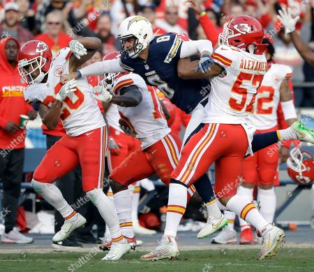 Stock Photo of San Diego Chargers punter Drew Kaser (8) leaps into Kansas City Chiefs blockers Steven Nelson (20) and D.J. Alexander (57), but did not enough to alter Tyreek Hill's, center, touchdown run on a punt return, during the second half of an NFL football game, in San Diego