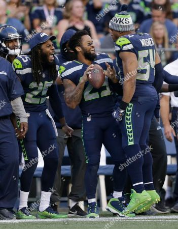 Stock Image of Seattle Seahawks' cornerback Richard Sherman, free safety Earl Thomas, center, and middle linebacker Bobby Wagner (54) react on the sideline in the second half of an NFL football preseason game against the Kansas City Chiefs, in Seattle. The Seahawks won 26-13