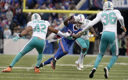 Buffalo Bills running back LeSean McCoy (25) avoids a tackle by Miami Dolphins linebacker Spencer Paysinger (42) during the first half of an NFL football game, in Orchard Park, N.Y