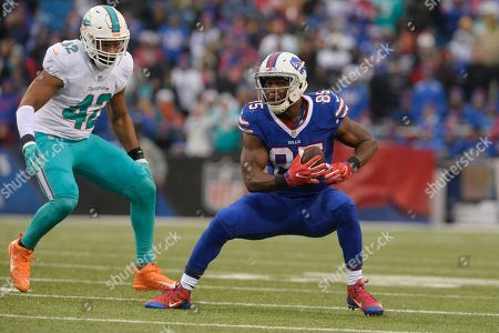 Miami Dolphins' Spencer Paysinger (42) closes in on Buffalo Bills' Charles Clay (85) after Clay makes a catch during the second half of an NFL football game, in Orchard Park, N.Y