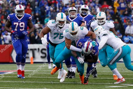Miami Dolphins linebacker Spencer Paysinger (42) tackles Buffalo Bills' LeSean McCoy (25) during the first half of an NFL football game, in Orchard Park, N.Y