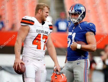 Cleveland Browns long snapper Charley Hughlett (47) talks with New York Giants long snapper Zak DeOssie (51) before an NFL football game, in Cleveland